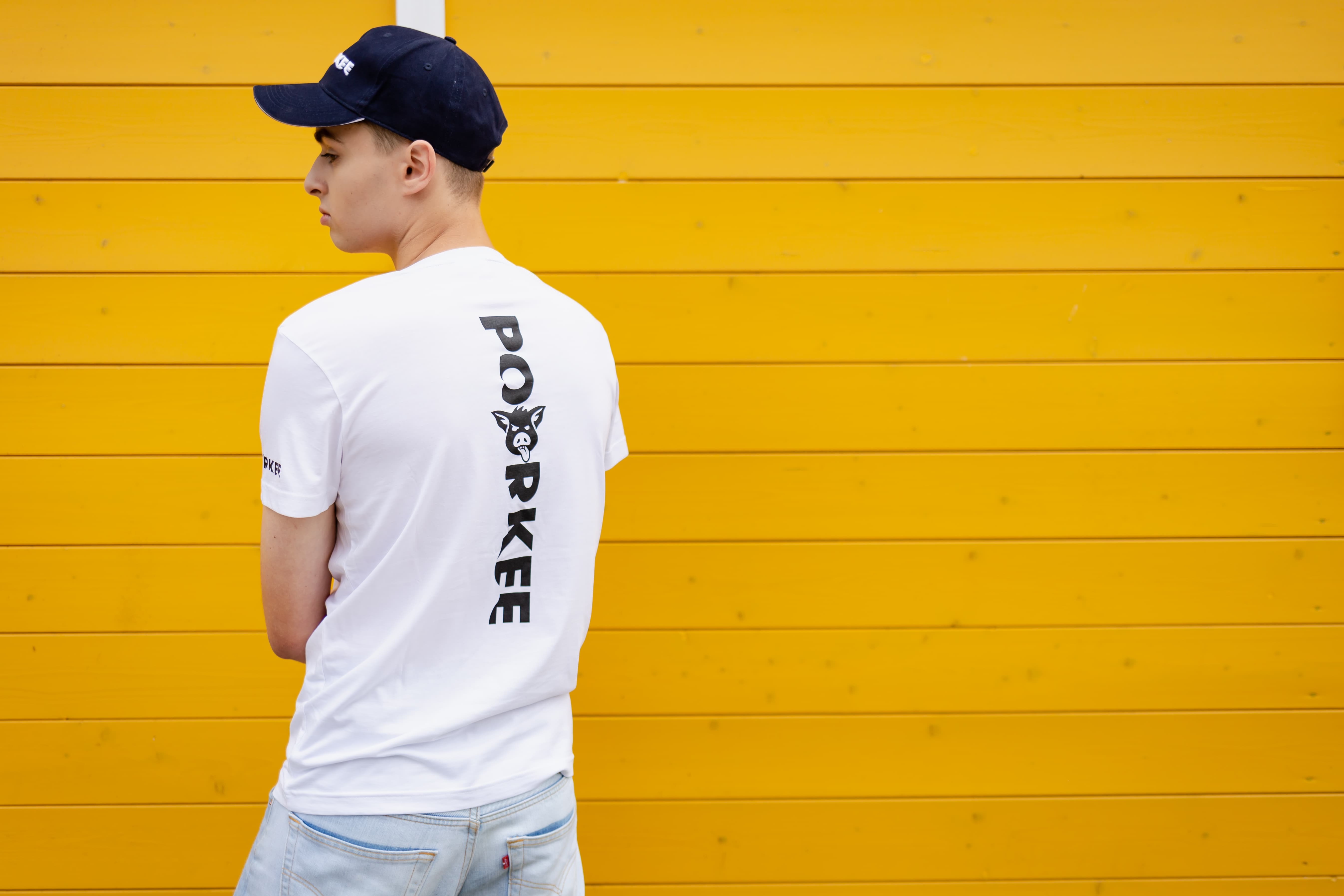 the boy presents a white T-shirt and a black cap on a yellow background