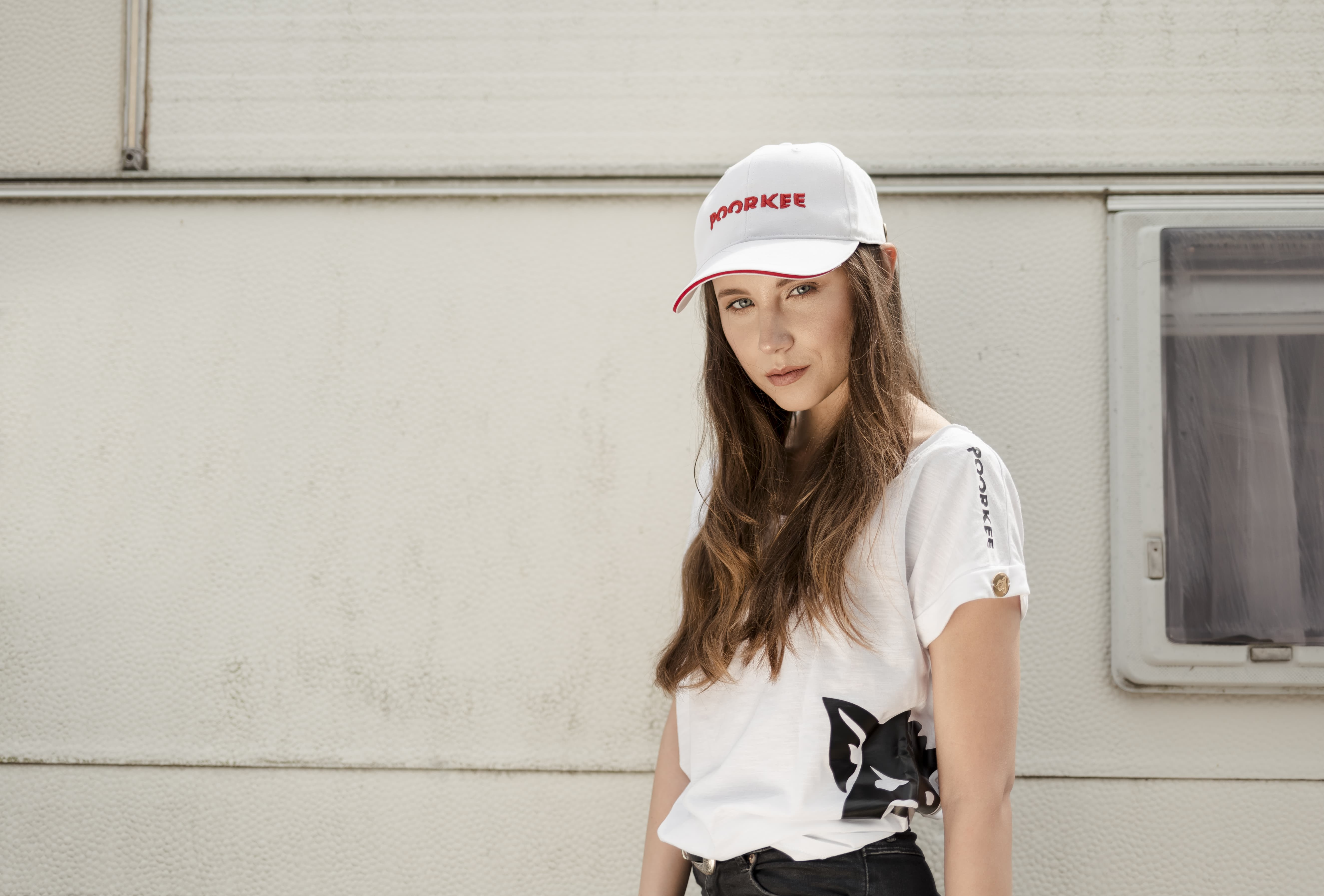 girl in long hair, a white baseball cap and a white T-shirt on the camper's background