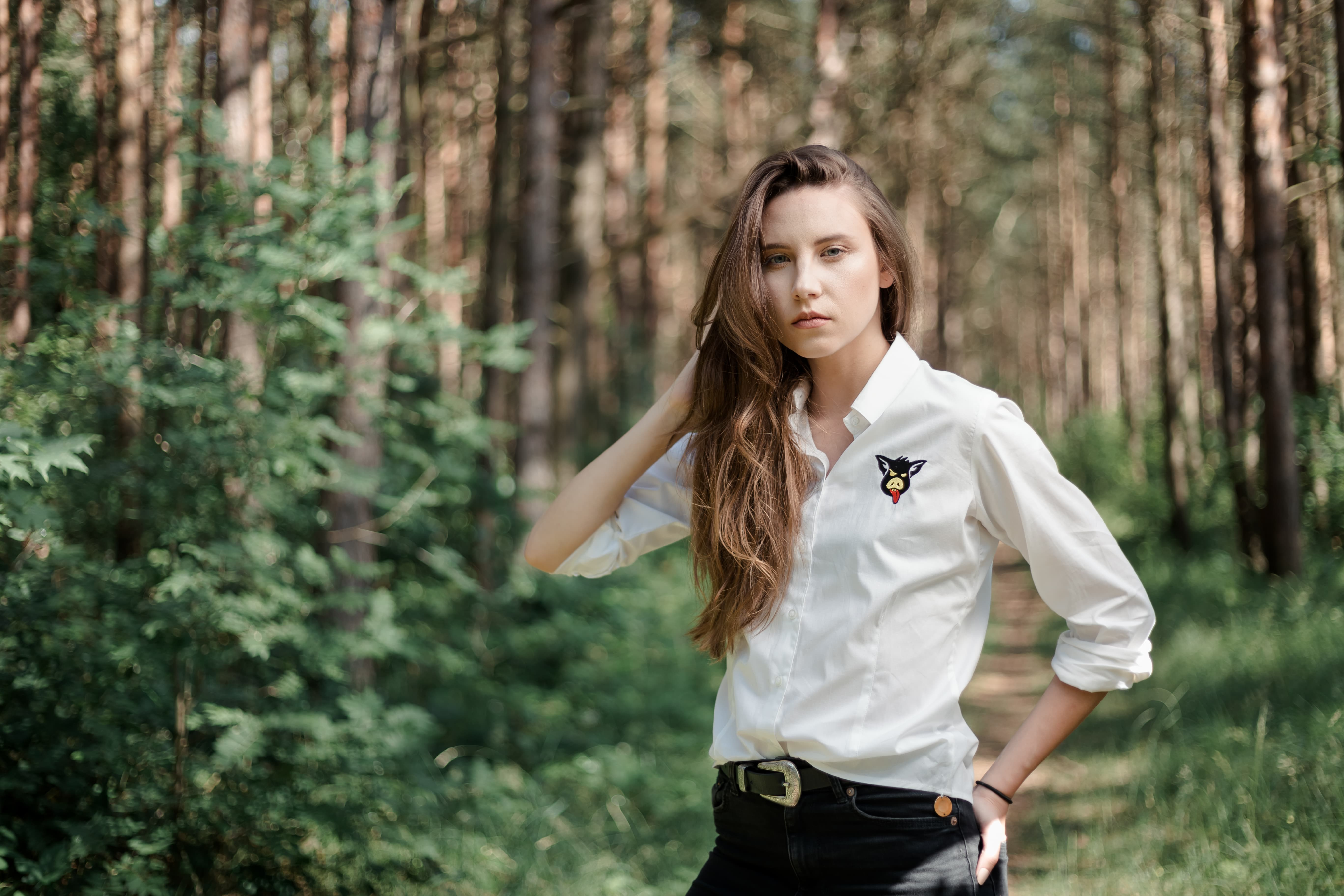 girl in a white shirt and long hair in the woods among the trees