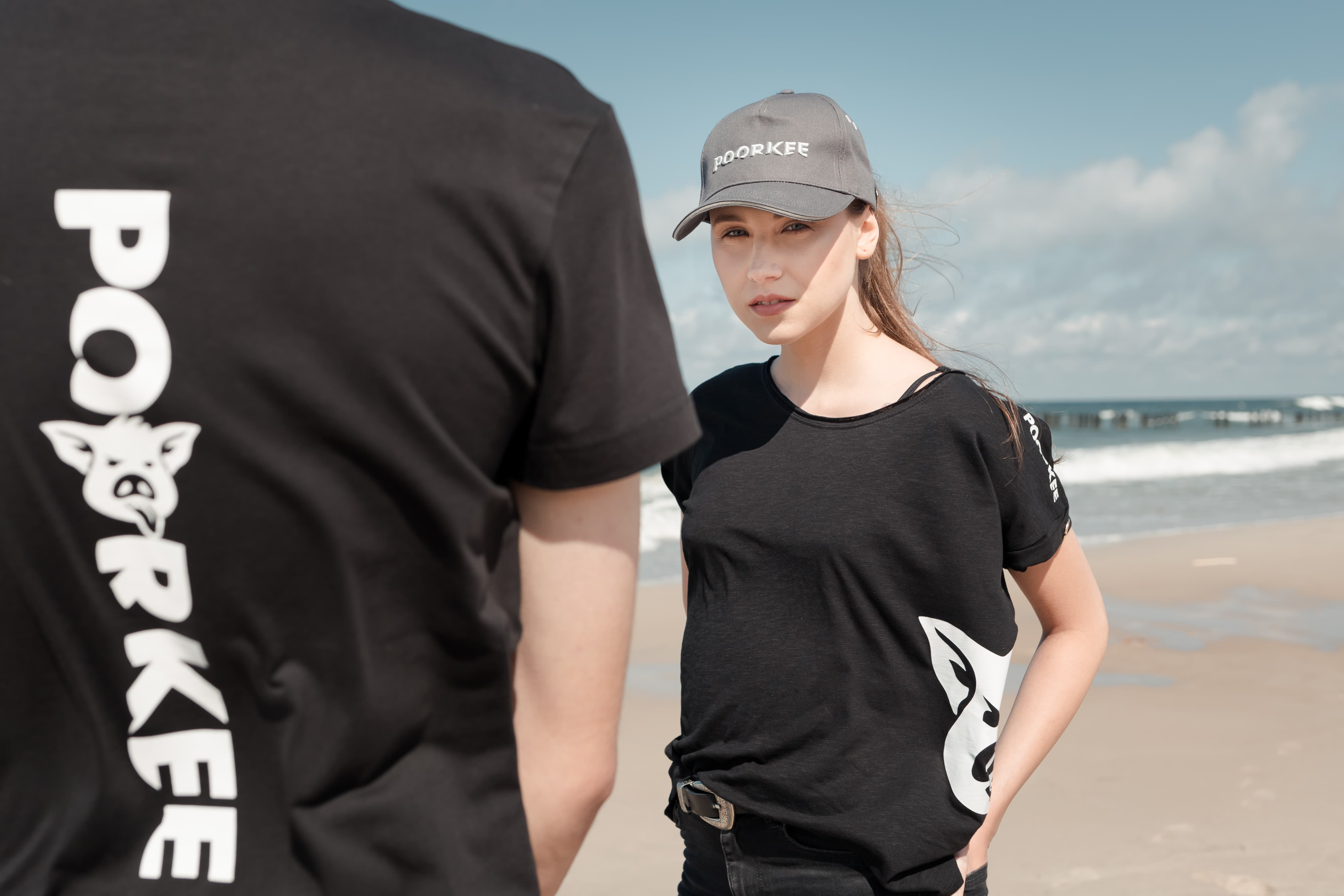 a girl in a black T-shirt and a gray baseball cap on the beach looks at the camera