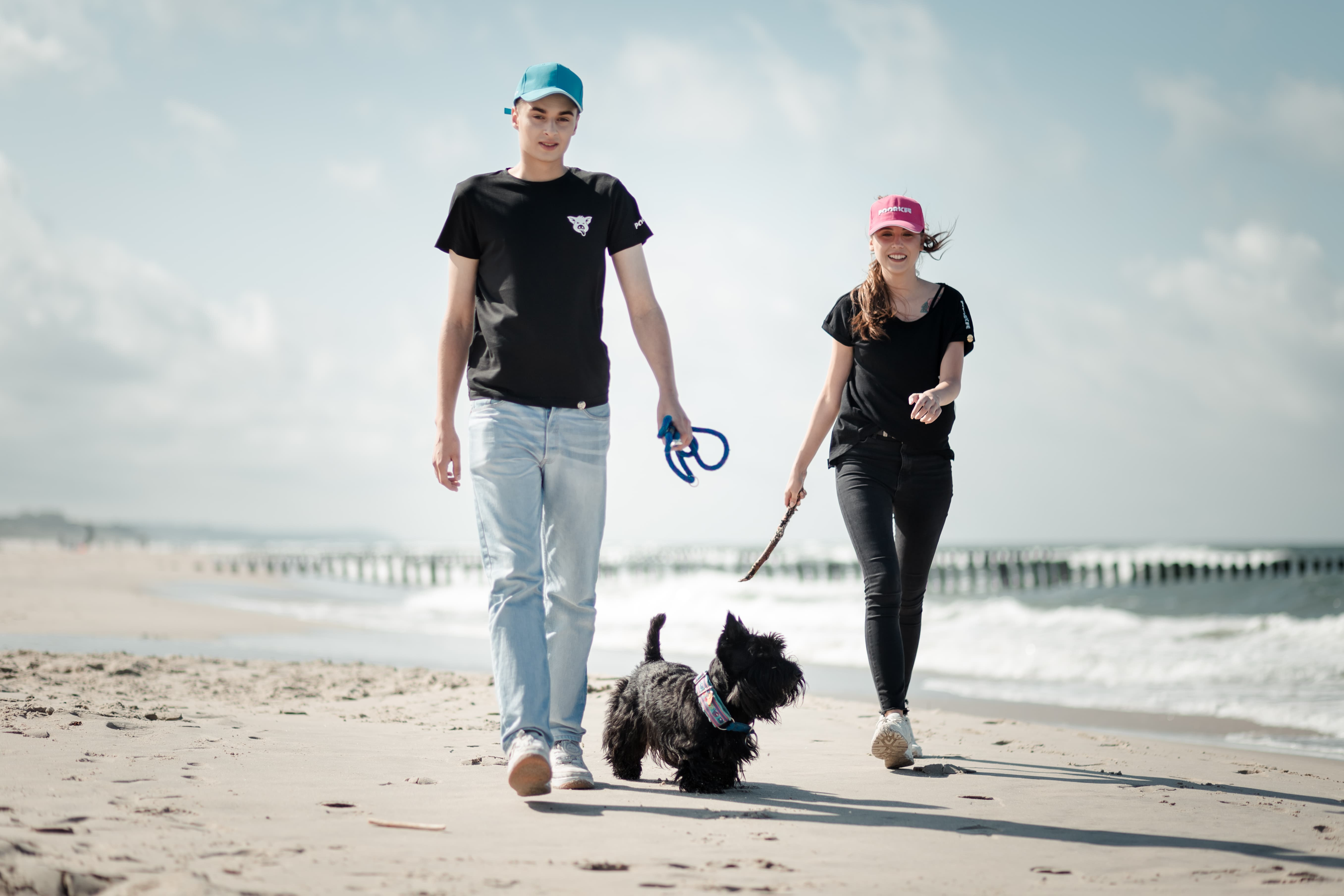 boy and girl are walking on the beach with a dog