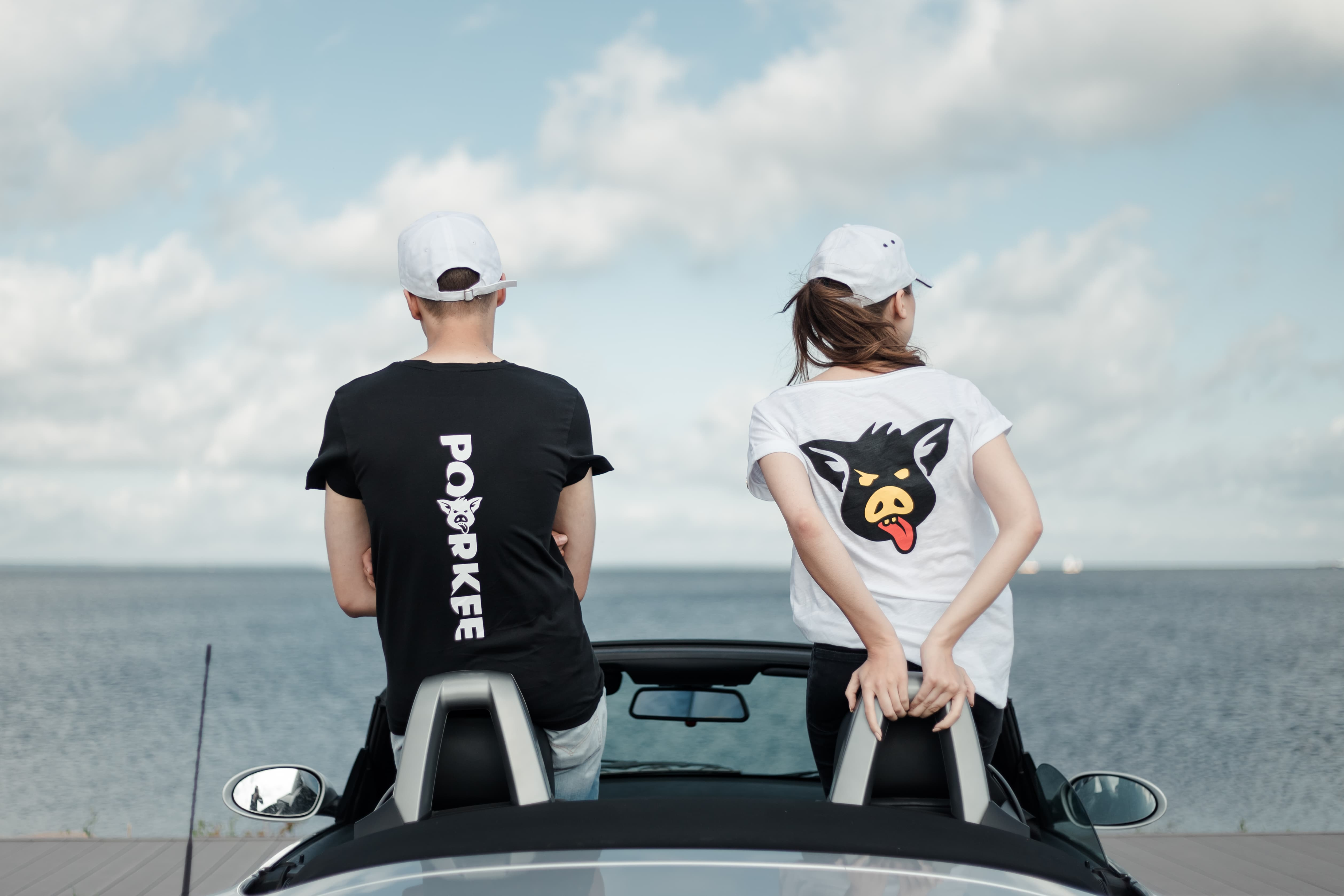 boy and girl are sitting in the car with the roof open and looking at the sea and the sky