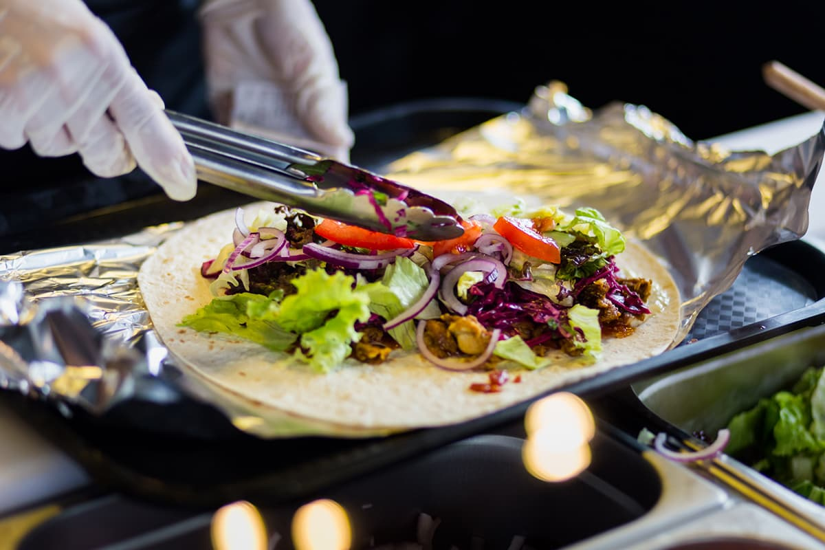 preparing a kebab: tortilla on a tray, sauce and meat and fresh vegetables on it