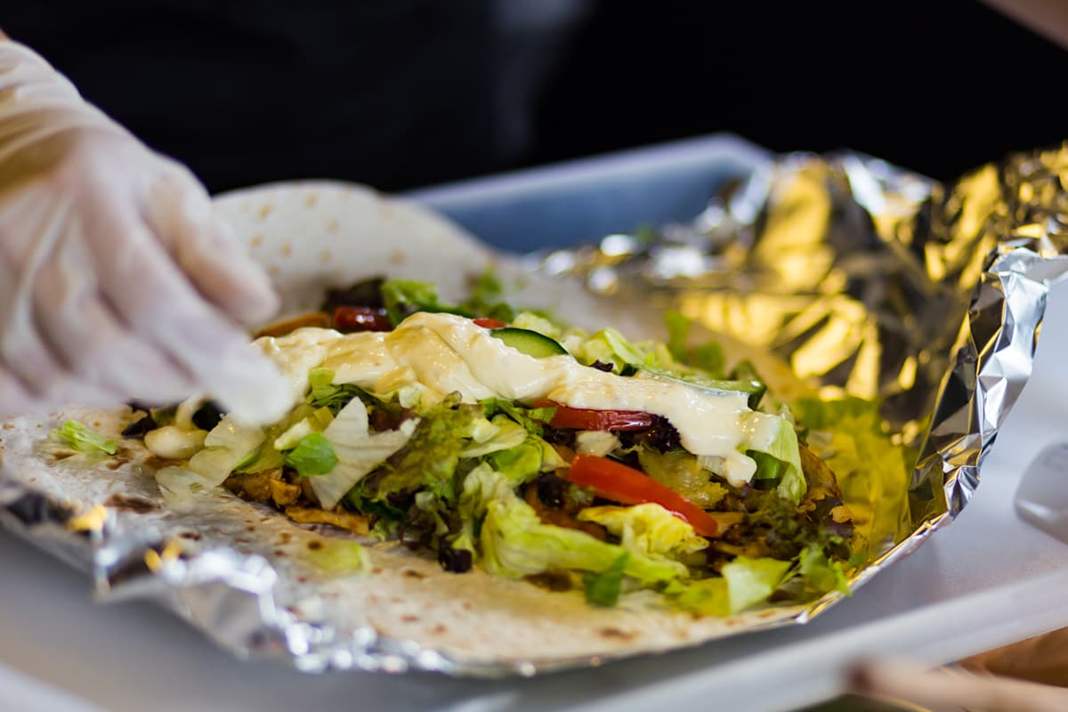preparing a kebab: a spread tortilla with toppings and a gloved hand