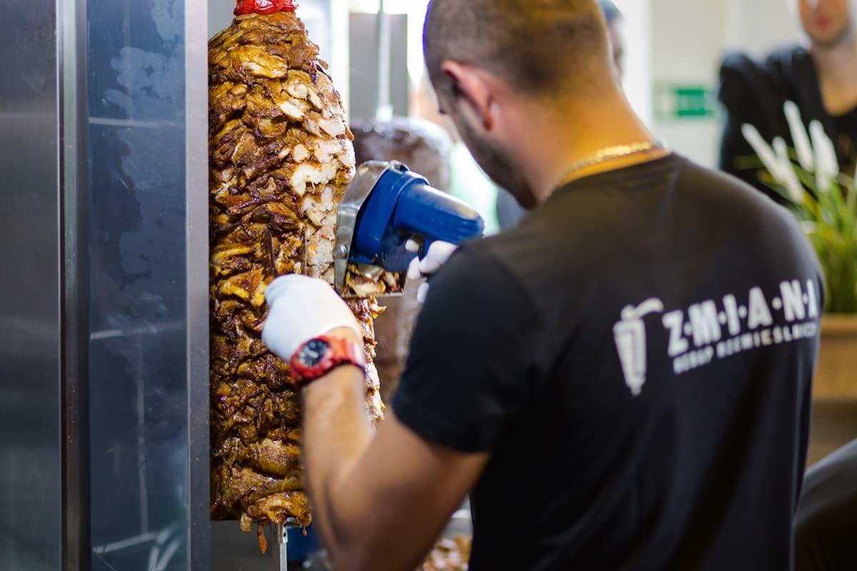 worker prepares meat for kebab (cuts)